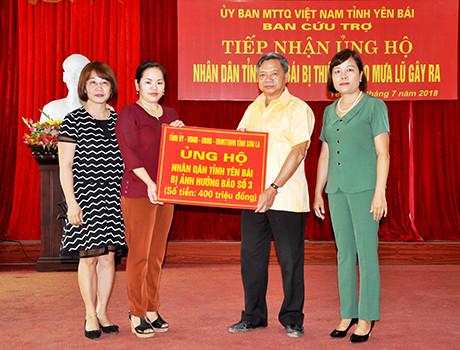 Đồng chí Giàng Thị Hương – Phó Chủ tịch Ủy ban Mặt trận Tổ quốc    tỉnh Sơn La trao kinh phí hỗ trợ cho tỉnh Yên Bái.