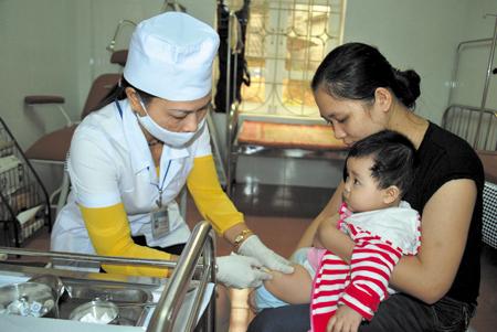 Cán bộ y tế phường Nguyễn Thái Học tiêm phòng sởi Rubella cho trẻ.