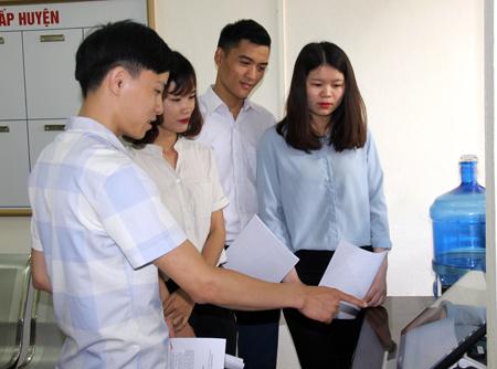 Cán bộ bộ phận tiếp nhận và trả kết quả huyện Văn Chấn hướng dẫn quy trình tra cứu dữ liệu trên phần mềm điện tử cho người dân.