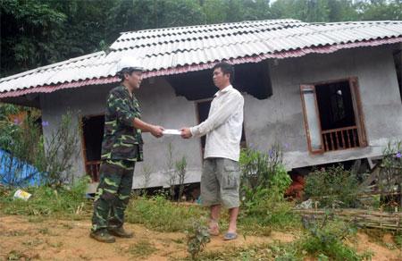 Đồng chí Nhuyễn Đình Chiến (bên trái) - Chủ tịch UBND huyện Trấn Yên thăm hỏi, động viên, trao tiền hỗ trợ cho hộ anh Lương Tiến Sĩ ở thôn Núi Vì, xã Hưng Khánh bị sập nhà hoàn toàn.