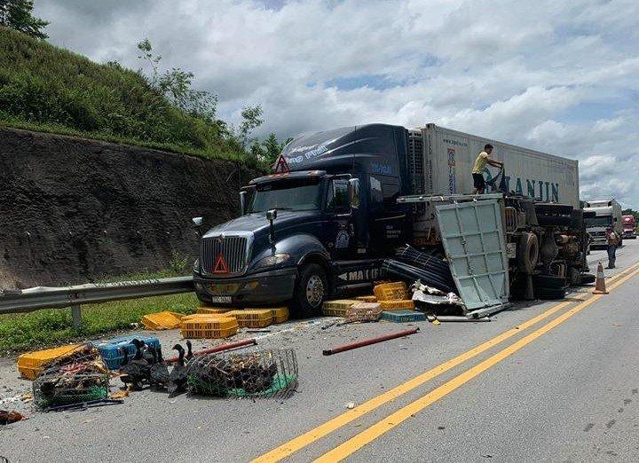 Sau cú va chạm với xe khách, xe tải đâm vào xe container rồi lật nghiêng trên đường.