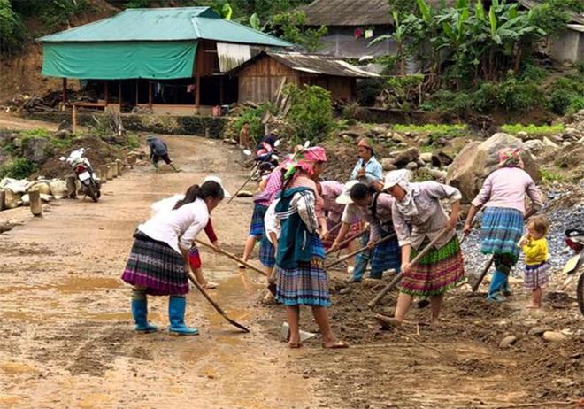 Người dân xã Xà Hồ tham gia dọn dẹp vệ sinh đường nông thôn sau mưa lũ.