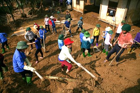 Cán bộ, giáo viên ngành giáo dục và đào tạo Văn Chấn giúp nhân dân khắc phục mưa lũ ở xã Sơn Lương tháng 7 năm 2018.