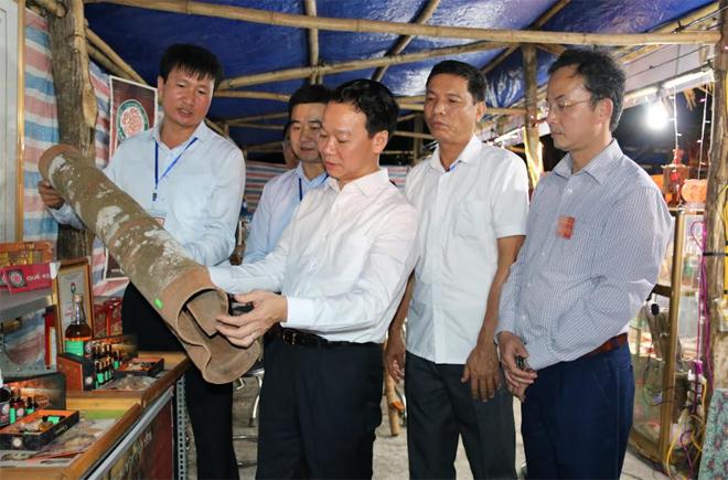 Đồng chí Đỗ Đức Duy - Phó Bí thư Tỉnh ủy, Chủ tịch UBND tỉnh trao đổi với lãnh đạo huyện Văn Yên về chất lượng sản phẩm quế vỏ được trưng bày tại Lễ hội đền Đông Cuông.