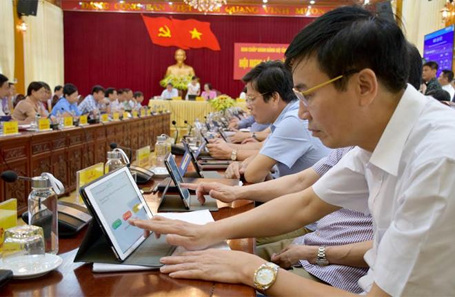 """Các đại biểu trong một cuộc họp ứng dụng """"phòng họp không giấy""""."""