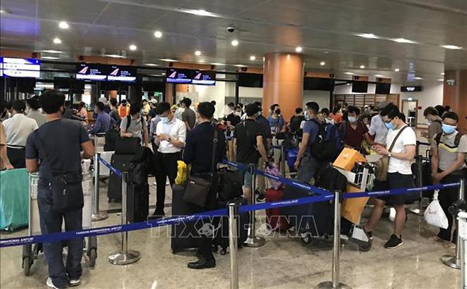 Công dân Việt Nam xếp hàng làm thủ tục lên máy bay về nước.