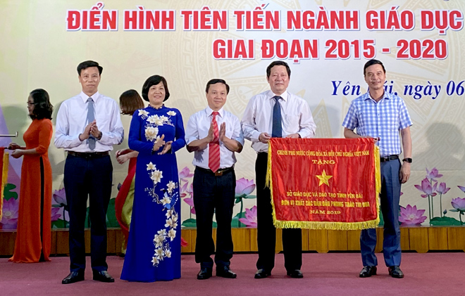 Duong Van Tien, Vice Chairman of the provincial People's Committee, and First Vice Chairman of the provincial Council for Emulation and Rewards presents the Government's emulation flag 2019 to the Department of Education and Training. (photo: Thanh Ba)