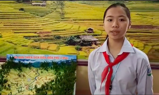 Vu Hoai Thuong, head of the student group, stands next to the model of the Dien Bien Phu Campaign.