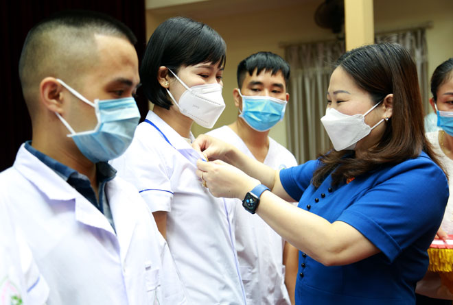 Vu Thi Hien Hanh, Vice Chairman of the People's Committee of Yen Bai, and deputy head of the Steering Committee for COVID-19 Prevention and Control, stick the Yen Bai logo to the white blouses of the medical staff before their leaving.  Bidding farewell to the medical staff sent to HCM City to assist the city in COVID-19 fight.