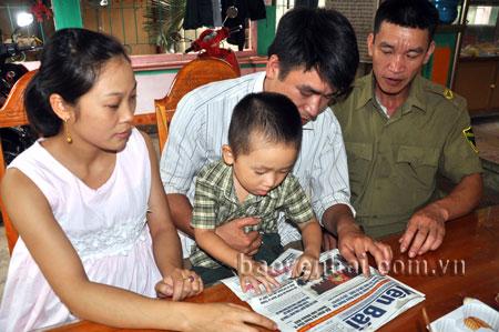 Bé Trần Danh Nhân đọc báo trước sự chứng kiến của nhiều người.