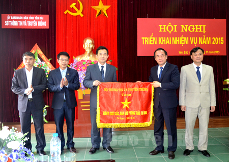 Đồng chí Tạ Văn Long - Phó Chủ tịch Thường trực UBND tỉnh (thứ hai, bên phải) trao cờ thi đua của Bộ Thông tin và Truyền thông cho Sở Thông tin và Truyền thông tỉnh Yên Bái năm 2014.