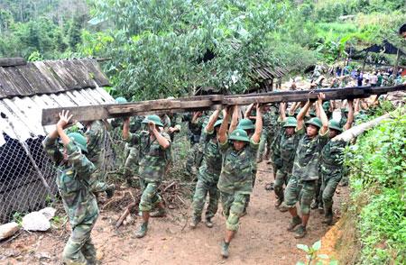 Hình ảnh người lính Cụ Hồ chung sức giúp người dân Mù Cang Chải dựng lại nhà sau trận lũ lịch sử.