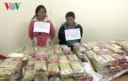 Vừ A Xìa (phải) và Mùa Thị Đớ (trái) cùng tang vật là 489 bánh heroin tại cơ quan công an.
