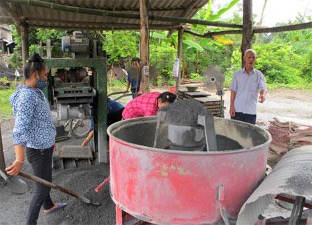 Ông Nguyễn Hữu Lưu trao đổi với công nhân trong quá trình sản xuất gạch bê tông.