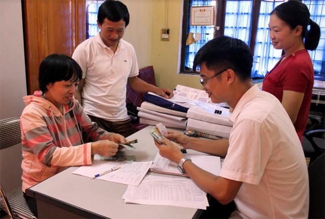 Bà Trần Thị Châm (người ngồi, bên trái) ở thôn Hồng Sơn, xã Sơn Thịnh nhận tiền hỗ trợ tại Phòng Nông nghiệp và Phát triển nông thôn huyện Văn Chấn.