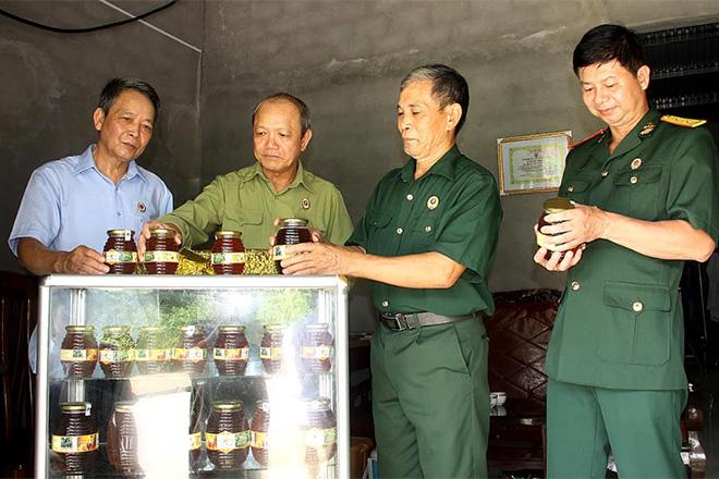 Thương binh Bùi Văn Đốc (thứ hai bên phải) giới thiệu sản phẩm mật ong với lãnh đạo Hội CCB thành phố Yên Bái.