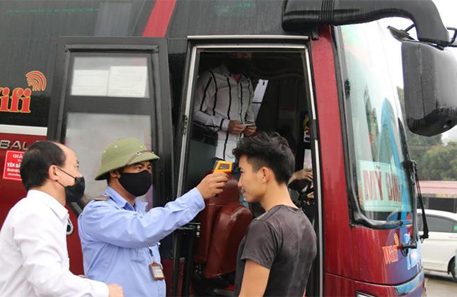 Ban Quản lý Bến xe khách Yên Bái đo thân nhiệt và phát khẩu trang cho hành khách.