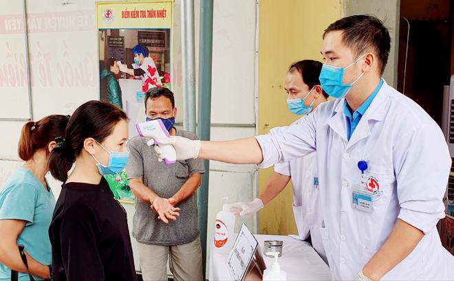 Để phòng, chống COVID-19, mọi người dân trên địa bàn tỉnh đều đeo khẩu trang và được đo thân nhiệt trước khi vào khám bệnh. (ảnh minh họa)