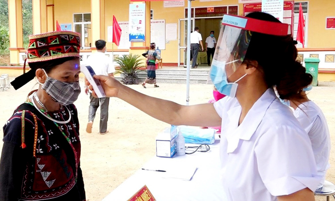 Cán bộ y tế Trung tâm Y tế huyện Văn Yên đo thân nhiệt cho người dân.