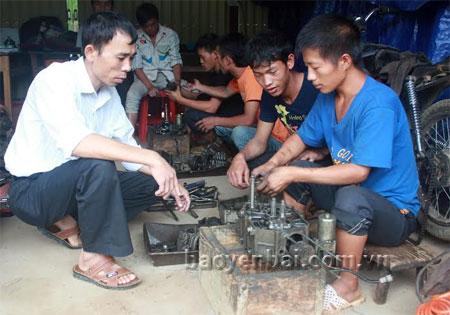 Thầy Trần Quốc Bình (bên trái) đang hướng dẫn học viên lớp sửa chữa xe máy.