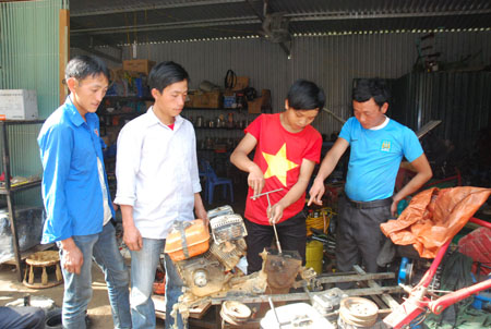 Anh Vàng A Chư (bên phải) dạy nghề sửa chữa máy nông cụ cho thanh niên các xã trong và ngoài huyện.