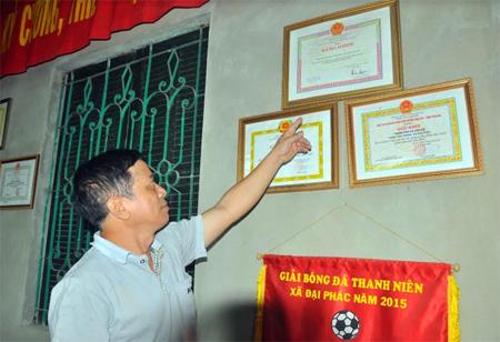 Ông Hoàng Văn Phong - Bí thư Chi bộ, Trưởng ban Công tác Mặt trận thôn Tân Thành, xã Đại Phác, huyện Văn Yên giới thiệu những thành tích mà thôn Tân Thành đã đạt được.