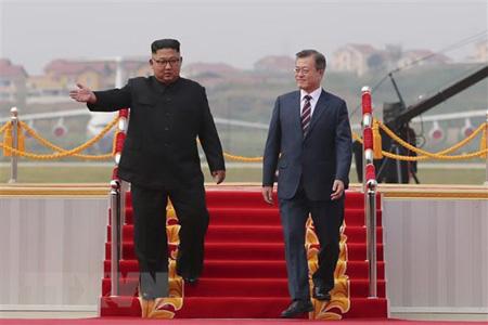 Nhà lãnh đạo Triều Tiên Kim Jong-un (trái) đón Tổng thống Hàn Quốc Moon Jae-in (phải) ở sân bay quốc tế Bình Nhưỡng ngày 18/9.