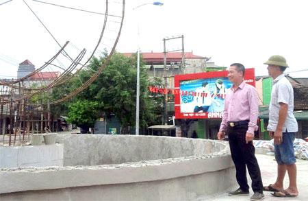 Anh Trần Văn Tuấn (đứng trước) kiểm tra tiến độ thi công các hạng mục công trình vườn hoa thuộc Dự án Chỉnh trang khu vực dốc Hoa Kiều thị xã Nghĩa Lộ.