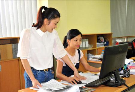 Cán bộ Chi cục Thuế thành phố Yên Bái trao đổi nghiệp vụ thu ngân sách.