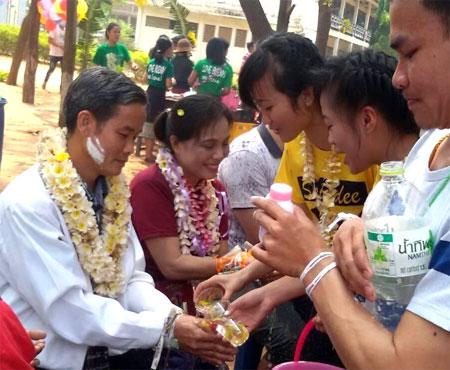 Cô Mai (thứ hai, trái sang) được các sinh viên Lào thực hiện nghi lễ buộc chỉ cổ tay nhân dịp tết cổ truyền Bunpimay của các bộ tộc Lào.