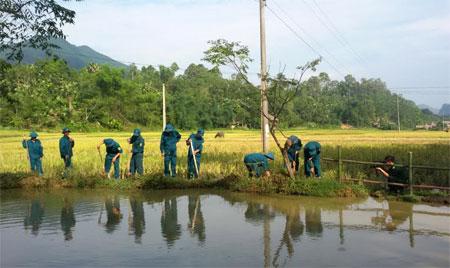 Lực lượng dân quân xã Liễu Đô giúp dân vệ sinh môi trường.