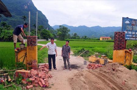 Người dân thôn Làng Mường sửa sang lại cổng làng văn hóa.