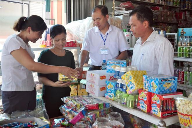 Cán bộ Phòng Y tế huyện Trấn Yên và lãnh đạo xã Đào Thịnh tuyên truyền về ATTP tại cơ sở kinh doanh của gia đình anh Nguyễn Tiến Công ở thôn 3.