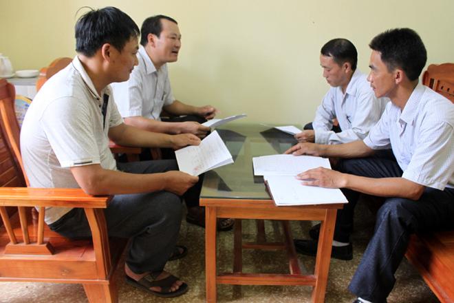Cán bộ Trung tâm Dịch vụ hỗ trợ và Phát triển nông nghiệp huyện Trạm Tấu (bên trái) trao đổi về phòng chống bệnh dịch tả lợn châu Phi với lãnh đạo xã Trạm Tấu.