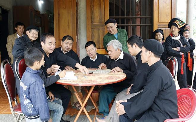 Ông Bàn Văn Kim hướng dẫn người dân và thế hệ trẻ trong thôn học chữ viết của người Dao.