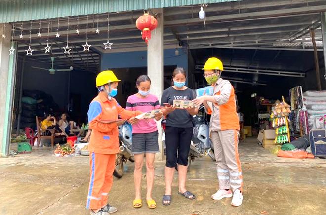 Cán bộ, nhân viên Công ty Điện lực Yên Bái tuyên truyền khách hàng thanh toán tiền điện không dùng tiền mặt.