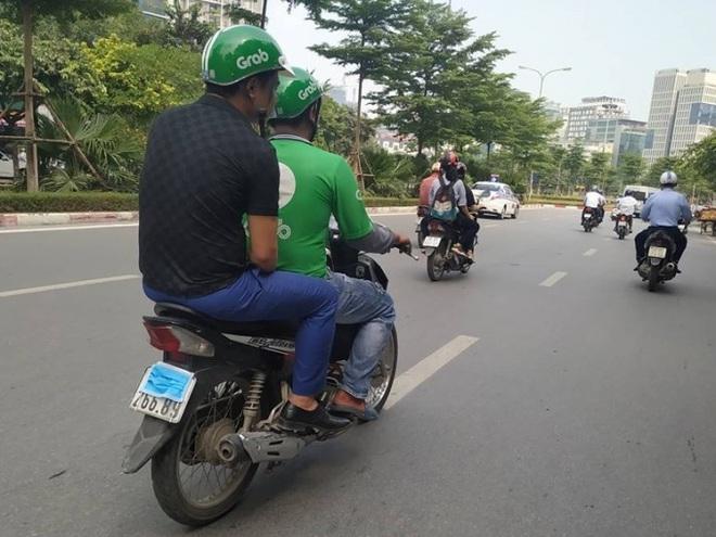 Một chiếc xe máy dùng khẩu trang che biển số khi tham gia giao thông